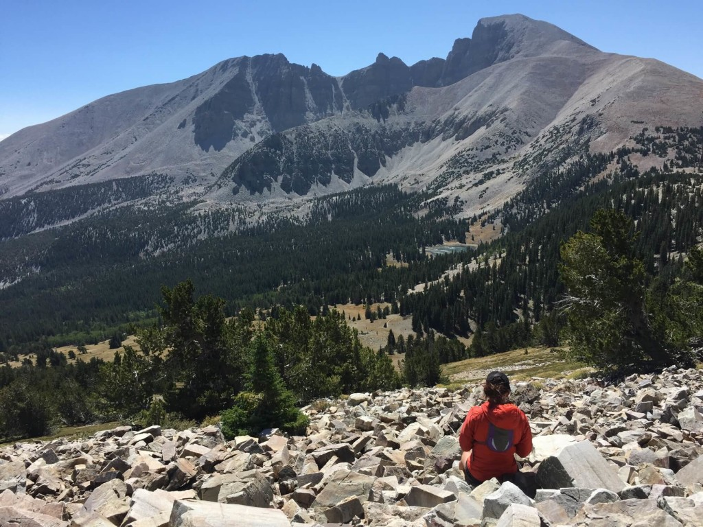 Female runner resting in boulder field below Wheeler Peak in Great basin National Park.