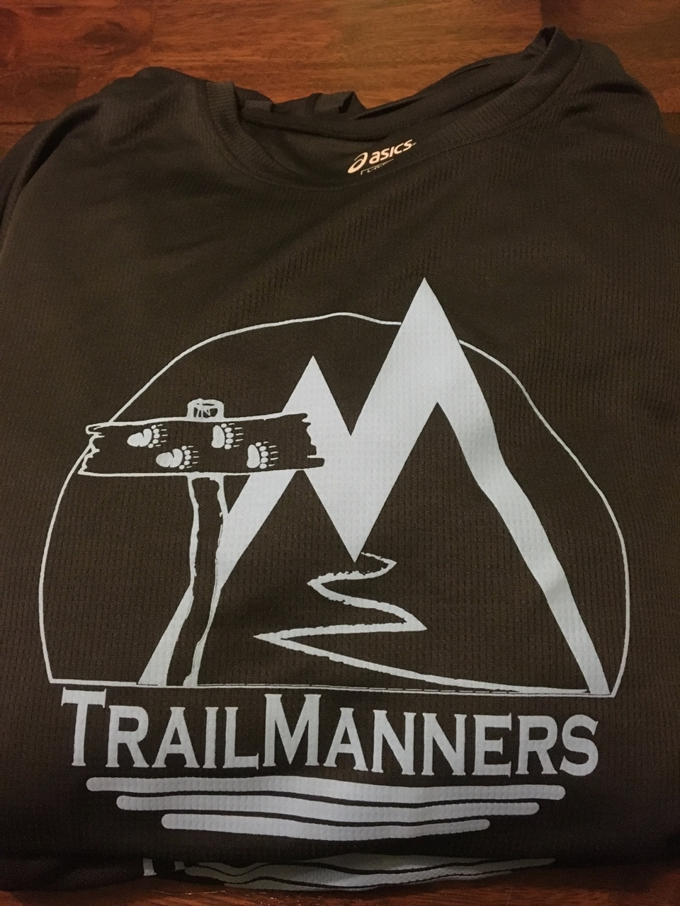Asics black tech tee with TrailManners logo.