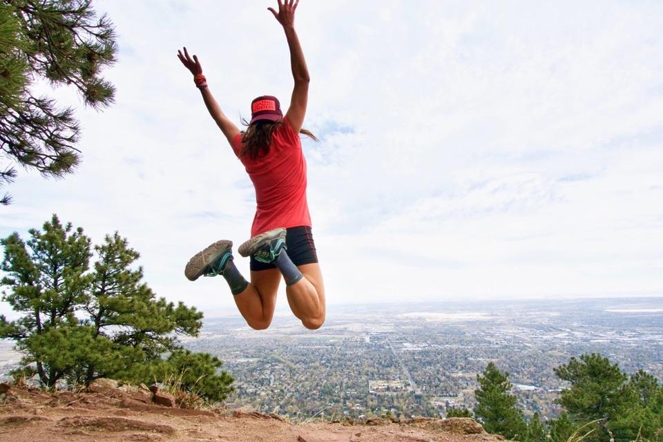 Gina Lucrezi jumping for joy on a Boulder Colorado trai.