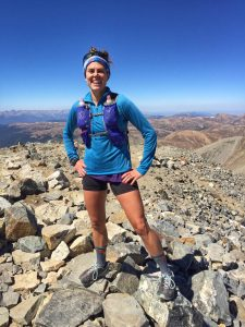 Gina Lucrezi smiling on top of a mountain.